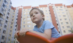 Child sits outside a block of flats