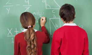 School children write on a blackboard