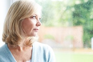 Sad middle aged woman looking out the window